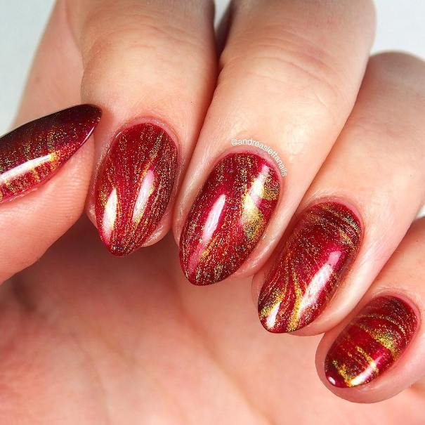 Watermarble glitter gold and red almond shape nail designs